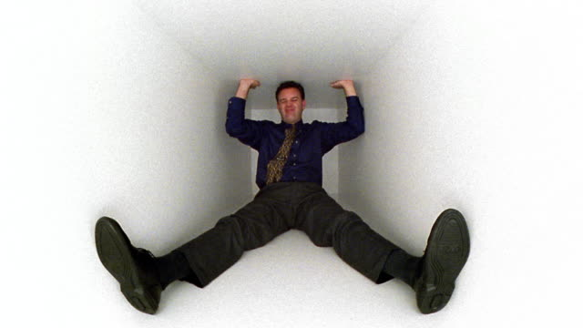 wide shot man sitting in white box with legs splayed, pressing against top with hands, making strained face - londonalight stock videos and b-roll footage