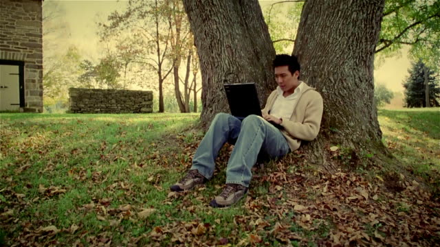 Wide shot man sitting under tree typing on laptop/ Solebury, Pennsylvania