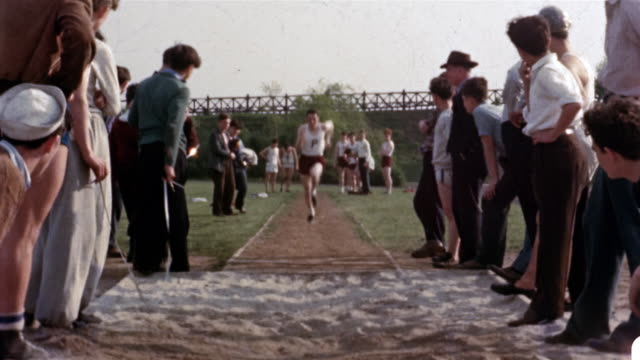 vídeos de stock e filmes b-roll de 1942 wide shot man sprinting down runway toward cam and leaping in long jump / spectators on side of runway - 1942