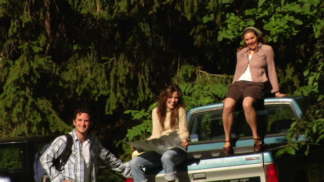 wide shot man standing next to two women sitting on back of pickup truck - male with group of females stock videos & royalty-free footage