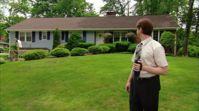wide shot man standing on front lawn with thermos looking back at suburban ranch house - ranch house stock videos & royalty-free footage