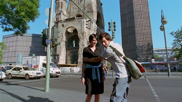 vídeos y material grabado en eventos de stock de wide shot man taking photo of woman in front of kaiser wilhelm memorial church / berlin - iglesia conmemorativa del emperador guillermo