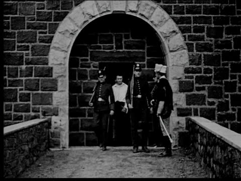 1916 b/w wide shot man to be executed leaving prison with guards - hinrichtung stock-videos und b-roll-filmmaterial