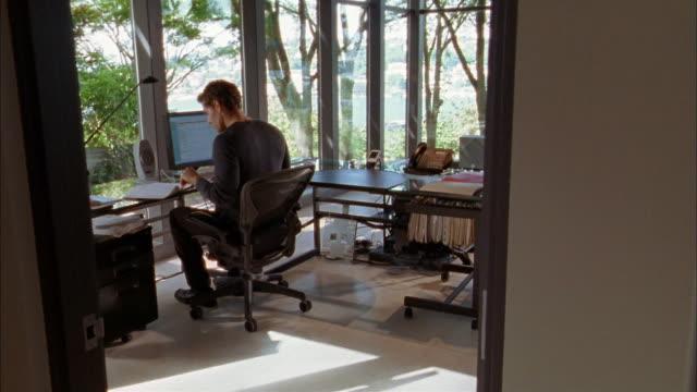 vidéos et rushes de wide shot man typing at computer in home office w/tv in corner - un seul homme d'âge moyen