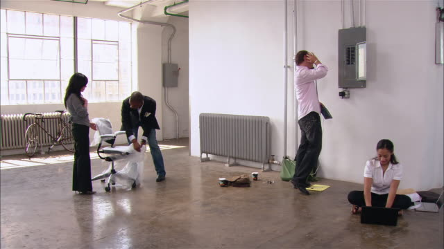 wide shot man unwrapping office chair as woman works on laptop on floor and man checks fuse box in empty loft/ brooklyn, new york - fuse box stock videos and b-roll footage