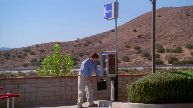 vídeos y material grabado en eventos de stock de wide shot man using phone book and dialing at roadside pay phone - directorio