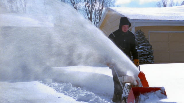 Wide shot man using snow blower to plow driveway