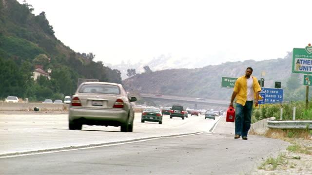 wide shot man walking along shoulder of route 2 carrying gas can / glendale, california - dejaover点の映像素材/bロール