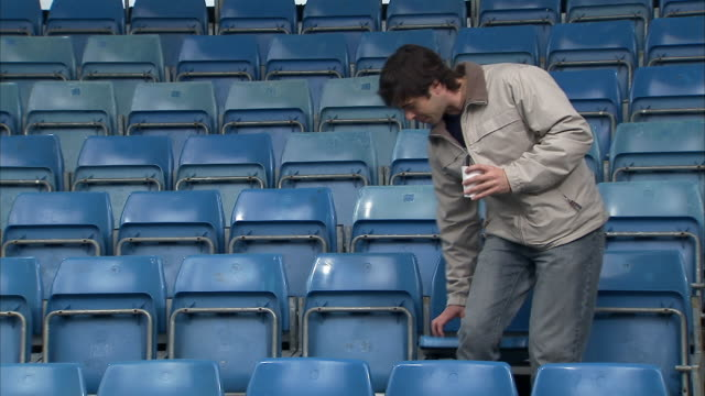 Wide shot man walking in and sitting in empty stadium/ England