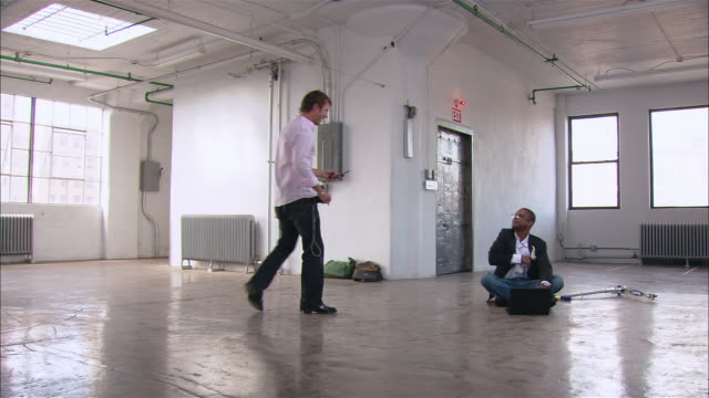 wide shot man walking in empty loft space looking at mobile phone as other man sits on floor with laptop/ brooklyn, new york - loft stock videos and b-roll footage