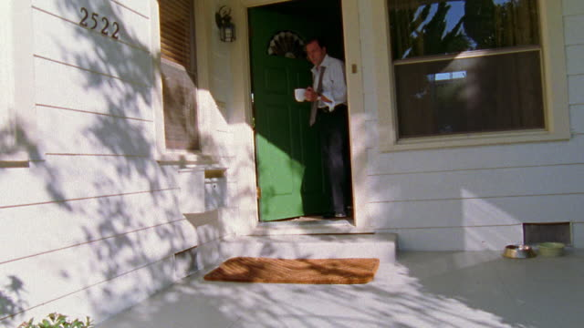 wide shot man walking out front door with necktie untied picking up newspaper / returning to house - untied stock videos and b-roll footage