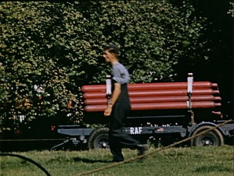 vídeos y material grabado en eventos de stock de wide shot man walking past cart stacked with royal air force bombs during war preparations / london england - cultura inglesa