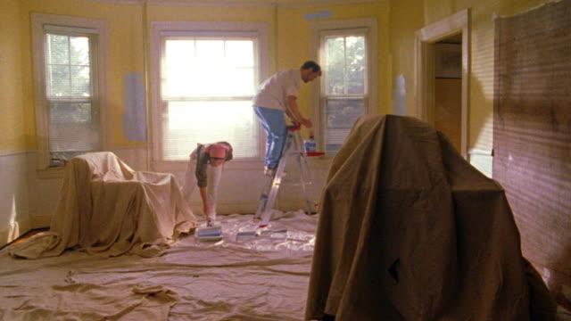 vídeos de stock e filmes b-roll de wide shot man + woman painting walls in drop cloth covered room - pano de protecção