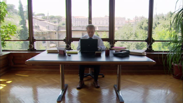 Wide shot man working on laptop at desk in front of window/ Rome