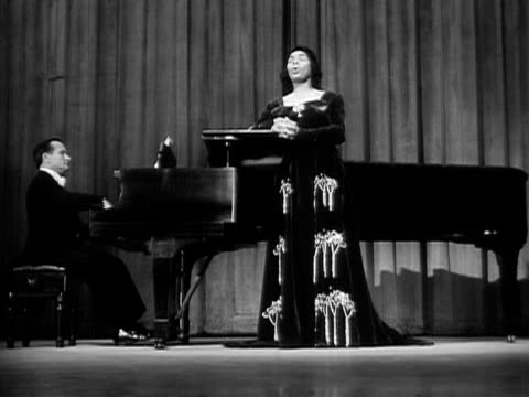 Wide shot Marian Anderson singing onstage next to pianist during her performance at The Town Hall/ Manhattan New York USA