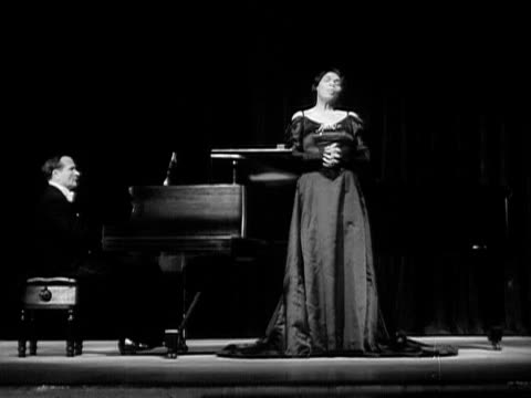 Wide shot Marian Anderson singing onstage next to pianist during performance/ USA