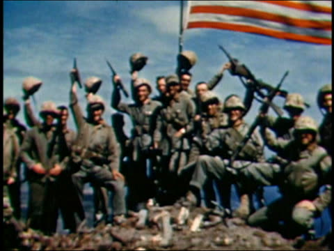 1945 wide shot marines posing and waving with guns upraised under american flag raised at iwo jima - iwo jima island stock videos & royalty-free footage