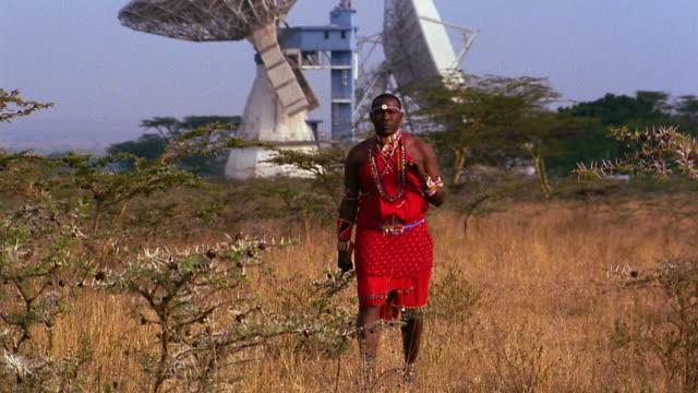 wide shot Masai tribesman walking on plain with satellite dishes in background / Kenya
