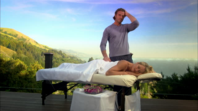 vídeos y material grabado en eventos de stock de wide shot masseur standing next to woman lying on massage table/ monterey country, california, usa - massage table