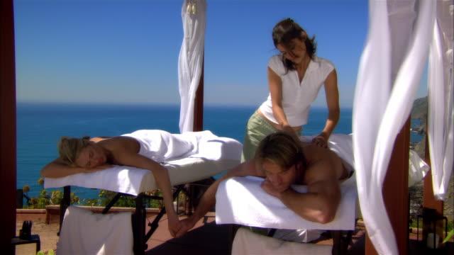 wide shot masseuse massaging couple at spa/ monterey county, california, usa - massagetisch stock-videos und b-roll-filmmaterial