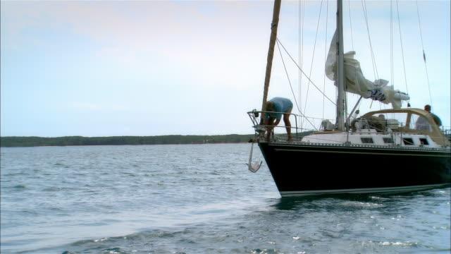 vidéos et rushes de wide shot mature man lowering anchor into sea from sailboat deck/ harbor island, bahamas - capitaine de bateau