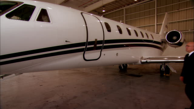 wide shot mature man opening door to private jet at opa locka airport/ miami, florida, usa - airplane hangar stock videos & royalty-free footage