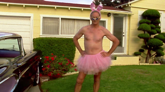 vídeos de stock e filmes b-roll de wide shot mature man wearing pink tutu, rabbit ears, and sunglasses on front lawn of suburban house - esquisito