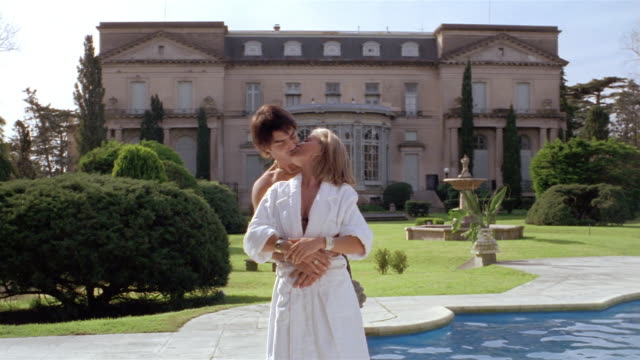 wide shot mature woman and young man embracing on pool deck outside her mansion / kissing / smiling at cam - 年の差カップル点の映像素材/bロール