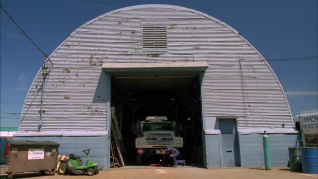 wide shot mechanic working beneath truck inside hangar door / ri - filling station attendant stock videos and b-roll footage
