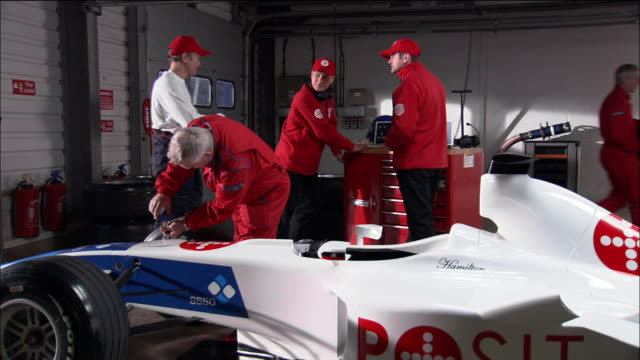 Wide shot mechanics working on Formula One race car / driver entering garage and greeting crew