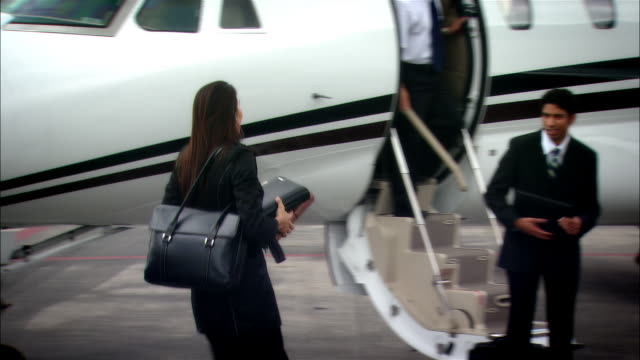 stockvideo's en b-roll-footage met wide shot - medium shot chauffeur opening luxury car door for businesswoman who kisses and greets colleagues then enters private jet at opa locka airport/ miami, florida, usa - overhemd en stropdas