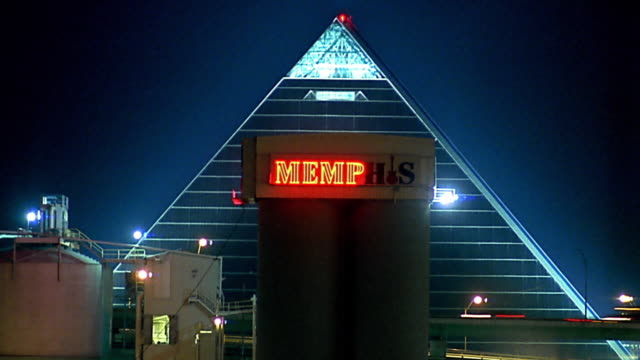 vídeos de stock e filmes b-roll de wide shot memphis sign lighting up in front of pyramid arena / time lapse traffice in background - memphis