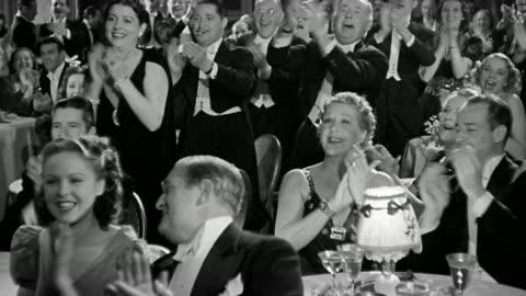 1940 wide shot men and women in formal restaurant standing + clapping for performance - applådera bildbanksvideor och videomaterial från bakom kulisserna