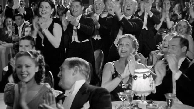 1940 wide shot men and women in formal restaurant standing + clapping for performance - applaudire video stock e b–roll