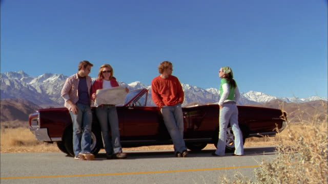 wide shot men and women standing by convertible on roadside / checking map - road map stock videos & royalty-free footage