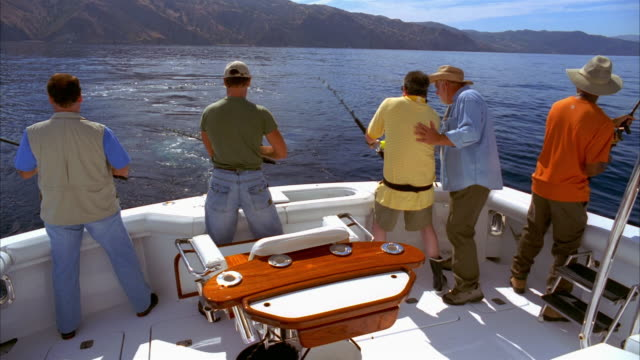 stockvideo's en b-roll-footage met wide shot men fishing from stern of boat/ men surround their friend as he struggles with fish on line/ california - noordelijke grote oceaan