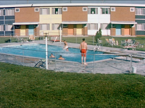 vídeos de stock e filmes b-roll de 1959 wide shot men jumping off diving board into pool at motel or apartment complex - 1950 1959