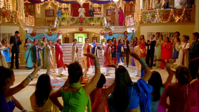 Wide shot men performing Bollywood-style dance number / people clapping along / group of women dancing with back to camera