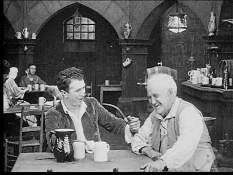 1916 B/W Wide shot Men talking in smoking in pub before group of peasants enter