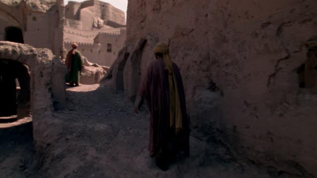1999 Wide shot Men walking through ruins of ancient Citadel of Bam/ Bam, Kerman Province, Iran