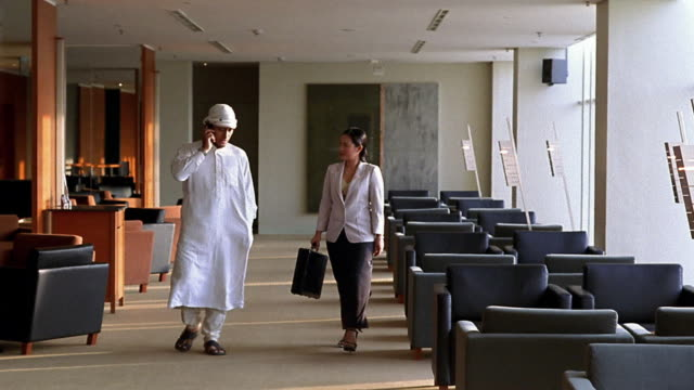 Wide shot Middle Eastern businessman and Asian businesswoman walking + talking in hotel lobby