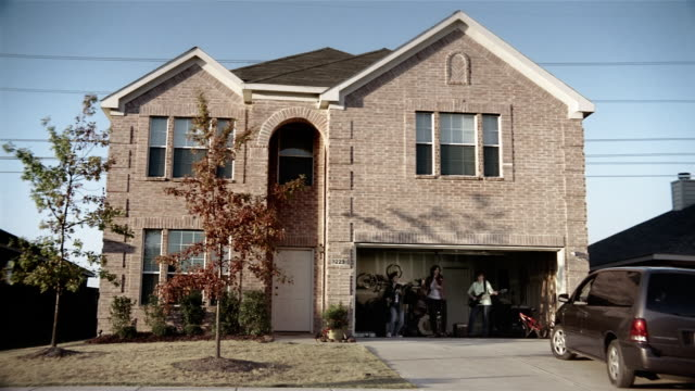 wide shot middle-aged women performing in garage band / man pulling up to house in minivan / closing garage door and carrying groceries to the house - performance group stock videos and b-roll footage