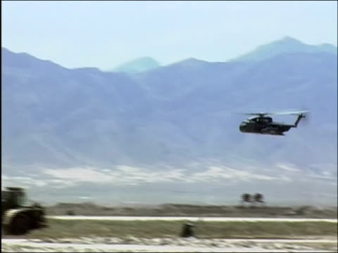 stockvideo's en b-roll-footage met wide shot military helicopter flying over bagram air base / bagram afghanistan / audio - bagram air base