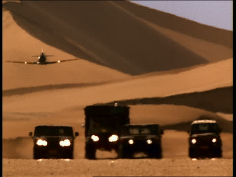Wide shot military jeeps and humvees driving in desert w/plane swooping low in background