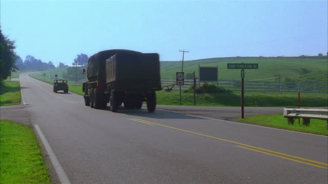 wide shot military vehicles traveling down country road / pan truck turning onto side road / virginia - 1995 stock videos & royalty-free footage
