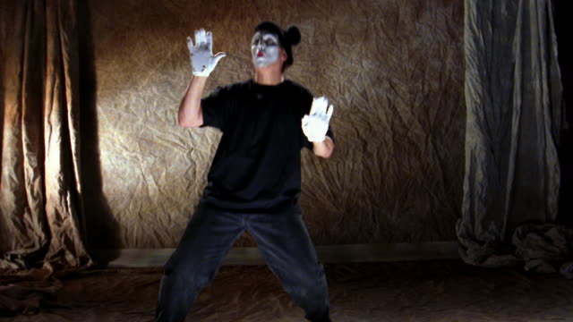 wide shot mime escaping imaginary box unsuccessfully - employment issues stock-videos und b-roll-filmmaterial