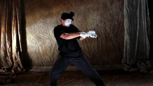wide shot mime playing tug of war with imaginary rope - パントマイム点の映像素材/bロール