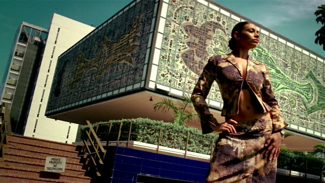 wide shot model posing in front of building with mosaic design - afro caribbean ethnicity stock videos and b-roll footage