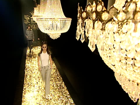 vídeos de stock, filmes e b-roll de wide shot models parading down catwalk below chandeliers during b&c european style fashion show rehearsal/ belgrade, serbia  - camiseta