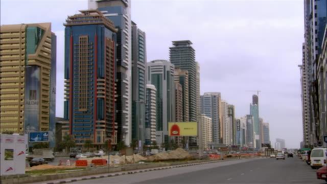 wide shot modern skyscrapers loom over automobile traffic on sheik zayed road, dubai, united arab emirates, january 2007 - 中東点の映像素材/bロール